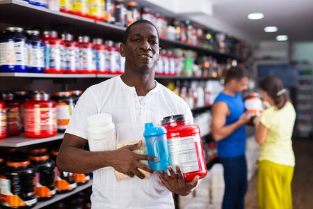 Glad athletic African man with jars of sports nutritional supplements bought in shop