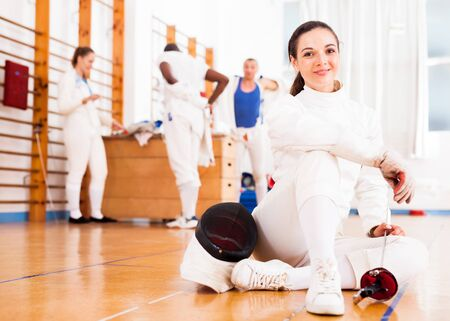 Smiling sporty young woman in uniform sitting on the floor at fencing training