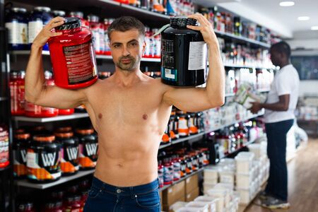 Bare-chested sportsman standing with cans of sports nutrition in store, demonstrating muscles