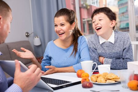 Happy ordinary couple with teenager son using laptop during breakfast at home