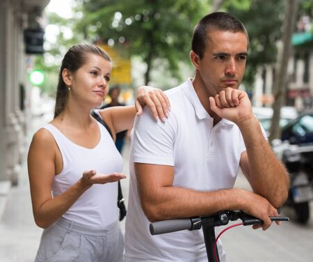Girl apologizing her offended boyfriend with electric scooter on street