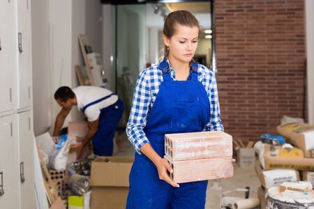 Friendly  positive  man and woman in work overalls carrying bricks during finishing work in room of public space