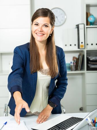Smiling and confident young woman giving hand for handshaking Stock fotó