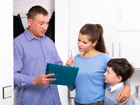 Young woman with cute preteen son participating in survey conducted at home by polite social male worker Banque d'images