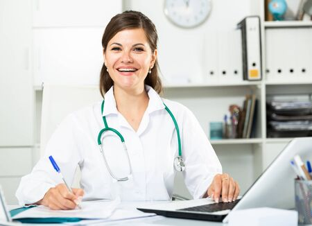 Cheetful woman doctor sitting at workplace with computer in her office