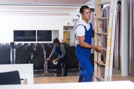 Trabajadores masculinos y femeninos en uniforme redecorando la sala de conferencias