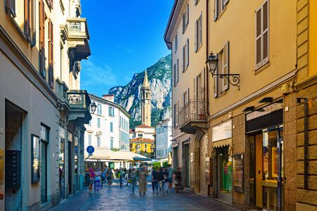 View of busy central street of Italian city of Lecco with gothic bell-tower of Minor Basilica of San Nicolo on background of San Martino mountain in sunny summer day
