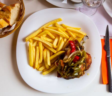 Close up of delicious baked with vegetables pork  with french fries, served at plate