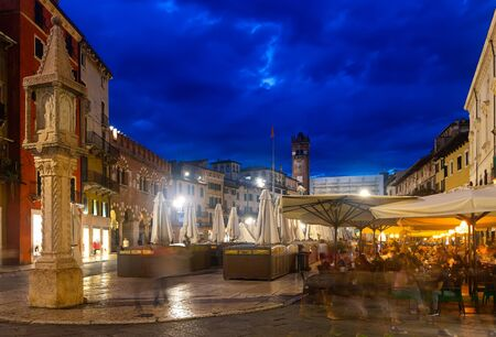 Picturesque cityscape of busy central streets of Verona in night lights, Italy