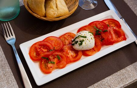 Plate with slices of tomatoes and  mozzarella cheese, dish of Italian cuisine Banco de Imagens