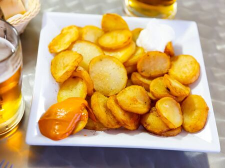 Dish of Spanish cuisine Patatas Bravas – fried potato with various sauces