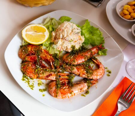 Dish of Mediterranean cuisine – shrimps with herb sauce and salad