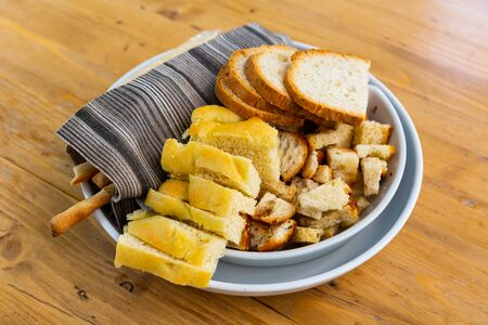 Various sliced bread, crispy croutons, grissini on one plate traditionally served in Italian restaurant