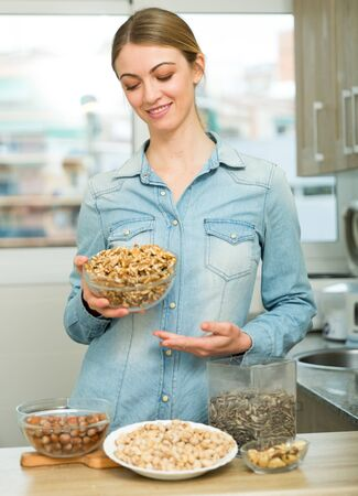 Portrait of happy housewife with nuts and sunflower seeds