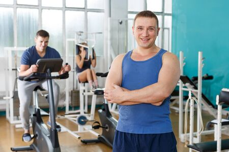 Muscular guy posing among sports equipment at gym Stok Fotoğraf