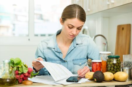 Portrait of woman working with papers at kitchen, worried about debts on bills