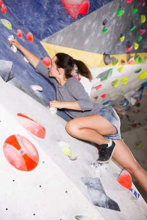 Portrait of confident female mountaineer climbing artificial rock wall without belay indoors Banco de Imagens