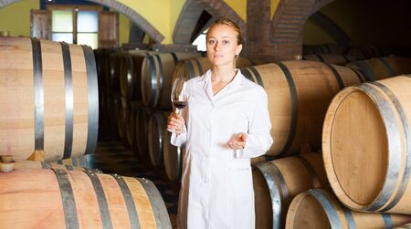 Serious young blonde woman in white robe checking ageing process of red wine