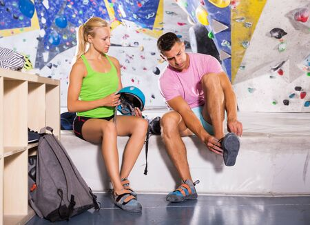 Athletic young man and woman equipping for climbing workout at bouldering gym