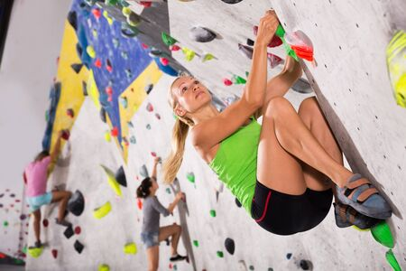 Positive female mountaineer climbing artificial rock wall without belay at bouldering gym Banco de Imagens