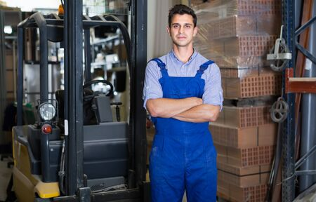 Portrait of confident working male in uniform on his workplace in building store.