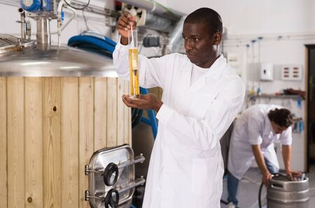 African american man brewer controlling quality of beer in flask in brew-house indoor