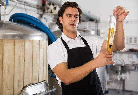 Worried man expert is standing with flask for beer and analizying quality in beer factory