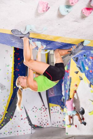 Young female alpinist practicing indoor rock-climbing on a artificial boulder without safety belts