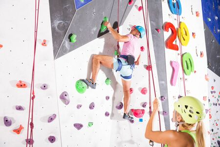 Male alpinist practicing indoor rock climbing on climbing wall in special equipment  Stock fotó
