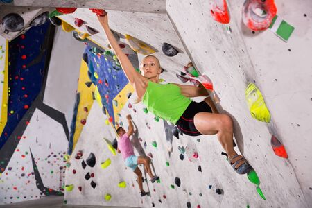 Young glad cheerful positive smiling sporty woman training at bouldering gym without special climbing equipment
