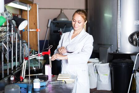 Young winery technician in white robe controlling fermantation process of wine