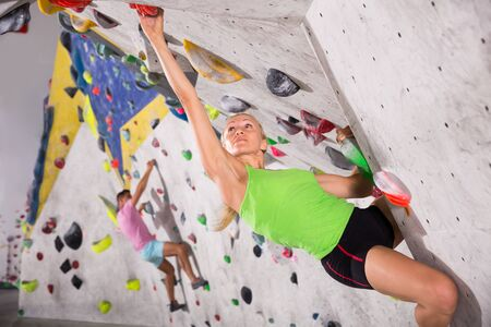 Young female mountaineer climbing artificial rock wall without belay in bouldering hall Banco de Imagens