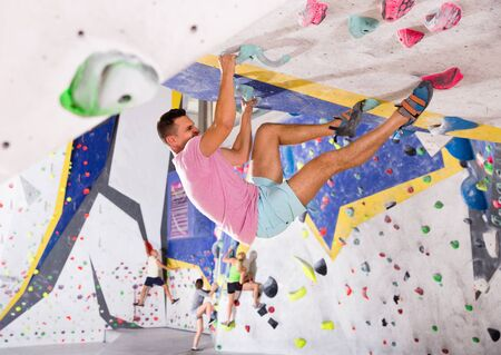 Positive male alpinist practicing indoor rock-climbing on artificial boulder without safety belts Banco de Imagens