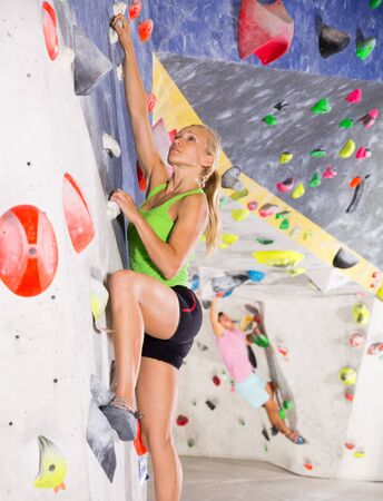 Confident female mountaineer climbing artificial rock wall without belay indoors