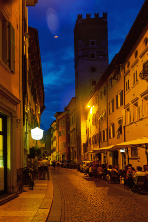 Busy typical street of ancient Italian city of Trento in autumn evening Editorial