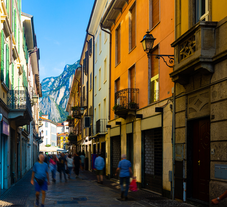 Typical busy narrow street of Italian city of Lecco on background of San Martino mountain in sunny summer day, Lombardy Editorial
