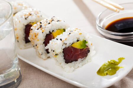 Image of delicious uramaki sushi with raw tuna at plate with soy sauce