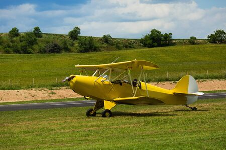 Yellow light biplane parked on green field on aerodrome Banque d'images