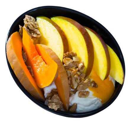 Juicy mango slices and delicate baked pumpkin with cereal flakes, nuts, dried fruits and yogurt. Isolated over white background