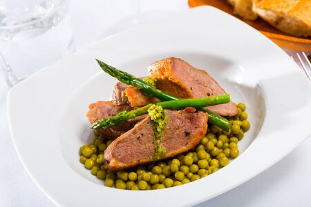 Delicious duck breast with steamed asparagus and canned green peas Фото со стока