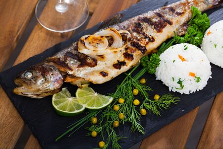 Delicious fried trout fish with white rice, fresh vegetables and lime on black serving board