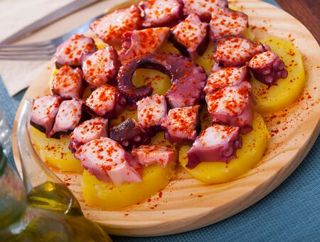 Traditional Galician fair dish of boiled octopus served with sliced cooked potatoes, smoked paprika and olive oil (Pulpo a la gallega) Banco de Imagens