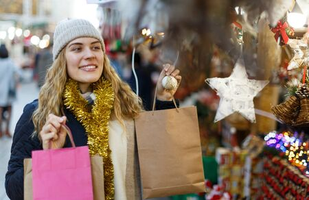 Portrait of smiling young woman holding paper bags with Christmas toys at fair