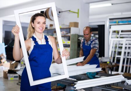 Smiling british girl in workwear with window frame from pvc profile standing in workplace Imagens