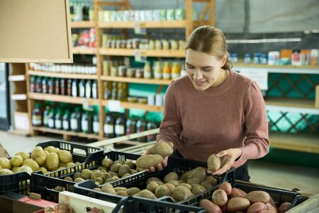 Smiling young woman choosing potatoes in grocery store