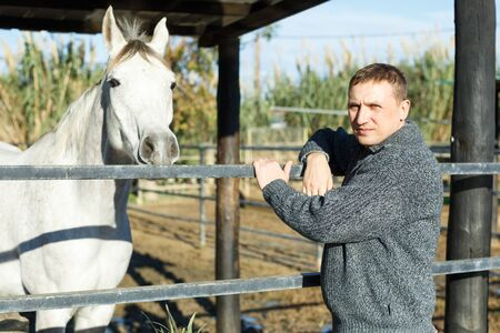 Portrait of cheerful man horse farm worker standing at stable