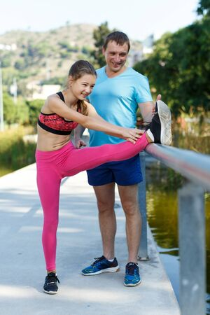 Slim preteen girl and her athletic father spending time together during workout outdoors