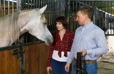 Portrait of couple man and woman standing at horse stable