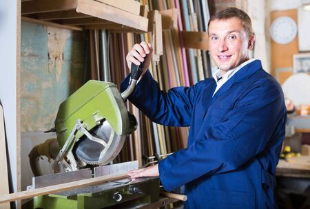 portrait of happy european man in uniform working on electrical rotary saw indoors