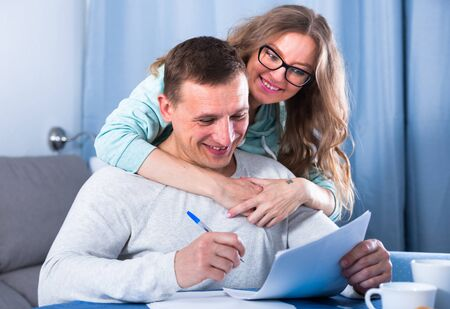 Smiling middle-aged husband and wife signing agreement papers together at home Standard-Bild